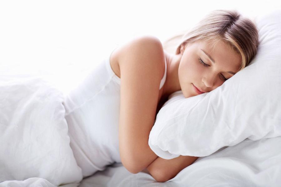 Junge Frau schläft mit Kopfkissen